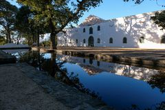 Cape Dutch style farm building at Groot Constantia, Cape Town, South Africa, reflected in a still pond in the early morning. royalty free stock images