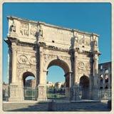 Constantine båge med coliseumen på bakgrunden Arkivfoto