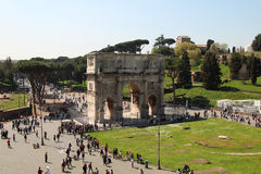 Constantine's arc during sunny day. Sunny day at the Constantine' arc , view from the Colosseum. Tourists taking photos of the scenery. The roman forum can be Stock Photography