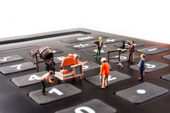 Constantly doing the best regarding business results. Fixing the problem concept, closeup of miniature figurine of workers repairing number buttons on a big royalty free stock photography