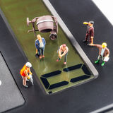 Constantly doing the best regarding business results. Fixing the problem concept, closeup of miniature figurine of workers repairing zero number on a big black royalty free stock image