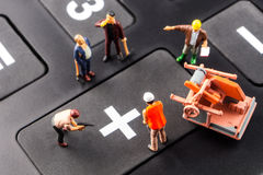 Constantly doing the best regarding business results. Fixing the problem concept, closeup of miniature figurine of workers repairing plus sign on a big black royalty free stock photography