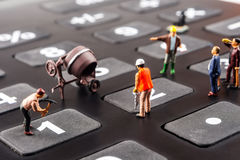 Constantly doing the best regarding business results. Fixing the problem concept, closeup of miniature figurine of workers repairing number buttons on a big royalty free stock images