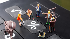 Constantly doing the best regarding interest rates. Constantly changing interest rates / fixing the problem concept, closeup of miniature figurine of workers royalty free stock photography