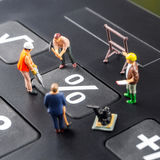 Constantly doing the best regarding interest rates. Constantly changing interest rates / fixing the problem concept, closeup of miniature figurine of workers stock image