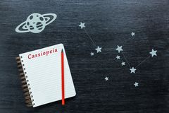 Constellations Cassiopeia. Zodiacal star, constellations Cassiopeia on a black background with a notepad and pencil stock photo