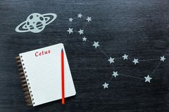 Constellations Cetus. Zodiacal star, constellations Cetus on a black background with a notepad and pencil royalty free stock photography