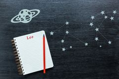 Constellations Leo. Zodiacal star, constellations Leo on a black background with a notepad and pencil stock image