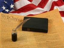 Constituição de Estados Unidos, Bíblia, pena de Quill no Inkwell, e bandeira Fotografia de Stock Royalty Free