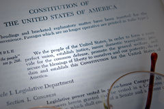Constitution. Of the United States being studied, with eye glasses and a beam of light highlighting the text Royalty Free Stock Image