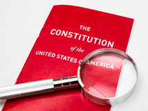 The Constitution of the United States of America. Red booklet of the US constitution with magnifying glass with white background.  Lists legal rights and Stock Images