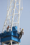 Constrction worker on crane. Construction worker leans off crane stock photography