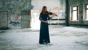 Construção abandonada com um violinista fêmea que joga o instrumento vídeos de arquivo
