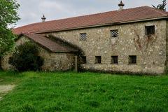 Construção abandonada velha em um gramado verde no meio da floresta imagens de stock royalty free
