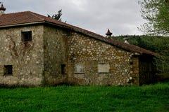 Construção abandonada velha em um gramado verde no meio da floresta foto de stock