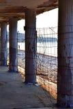 Construção abandonada velha na praia Colunas resistidas ao lado do mar azul imagens de stock royalty free