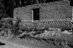 Construção abandonada velha situada no campo entre árvores altas e fugas da sujeira foto de stock royalty free