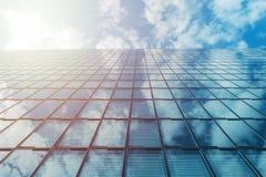 Construção alta do vidro da elevação do negócio moderno e céu azul com nuvens e sol imagem de stock royalty free
