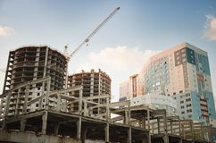 Construção alta sob a construção e a cidade ao redor no céu nebuloso fotografia de stock royalty free