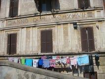 Construção antiga do distrito Garbatella em Roma com alguma lavanderia suspendida esse ` s que seca acima Fórum romano do Th Fotos de Stock