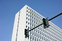 Construção branca com um sinal verde no primeiro plano Fotografia de Stock