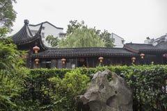 Construção chinesa do emblema atrás das plantas verdes fotografia de stock