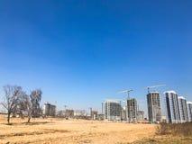 Construção com a ajuda dos guindastes de construção do concreto reforçado alto, painel, molde-quadro, casas do quadro-bloco, cons imagem de stock