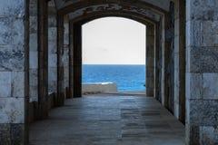 Construção com a costa rochosa do arco & o mar translúcido imagens de stock royalty free