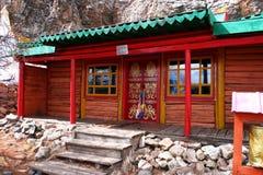 Construção com a porta vermelha pintada dos símbolos budistas tradicionais no monastério de Tovkhon, província de Ovorkhangai, Mo foto de stock