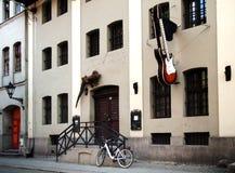 Construção com sinal da guitarra e estátua do geco na parede Fotografia de Stock Royalty Free