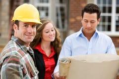 Construção: Contratante com agentes atrás Fotografia de Stock Royalty Free
