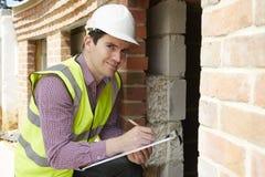 Construção da casa de Checking Insulation During do arquiteto imagens de stock royalty free