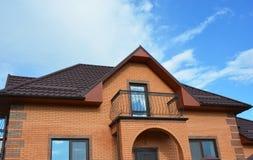 Construção da casa do tijolo da construção com tipos diferentes de projeto do telhado do sótão e de balcão do metal Imagem de Stock