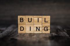 A construção da palavra feita de cubos de madeira brilhantes com letras pretas o Foto de Stock