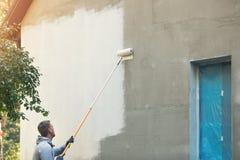 Construção da pintura do pintor de casa exterior com rolo Fotos de Stock Royalty Free