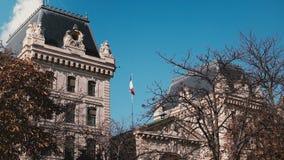 Construção da prefeitura da polícia em Paris, França Voo francês da bandeira no céu azul no dia ensolarado Marco europeu históric vídeos de arquivo
