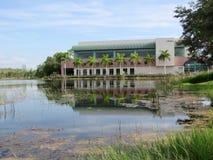 Construção de biblioteca que reflete através de um lago imagem de stock