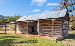 A construção de exploração agrícola pioneira faz dos logs e da árvore inoperante Fotografia de Stock Royalty Free