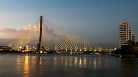 A construção de ponte no crepúsculo e reflexão do rio na noite Imagens de Stock Royalty Free
