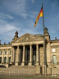 Construção de Reichstag em Berlim, em Alemanha e na bandeira alemão na parte dianteira foto de stock