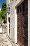 Construção de tijolo antiga na barra velha da fortaleza, Montenegro Porta de madeira antiga e lanterna velha imagens de stock