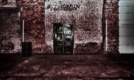 Construção de tijolo com uma grande porta do ferro Foto de Stock