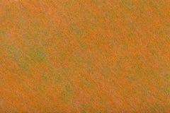 Construção de um fundo alaranjado brilhante com claro - pontos verdes da tela de feltro, close up Textura da matéria têxtil matt  imagem de stock royalty free