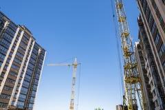 Construção de um prédio com um guindaste Construção civil usando o molde Guindastes e construções contra fotografia de stock