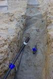 Construção de um sistema de fonte novo da água, tubulação na trincheira Fotografia de Stock