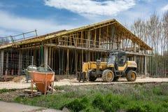 Construção de uma casa unifamiliar com ferramentas profissionais: misturador concreto, andaime e uma empilhadeira fotos de stock royalty free