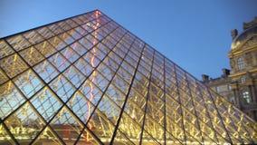Construção de vidro da pirâmide do Louvre iluminada brilhantemente por luzes na noite, Paris filme