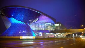 Construção de vidro iluminada moderna passada da condução de carros, tempo da noite, tempo chuvoso filme