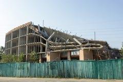 Construção destruída atrás de uma cerca verde foto de stock royalty free