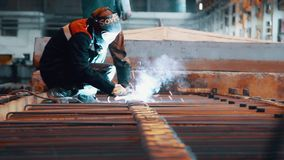 Construção do metal de soldadura do trabalhador na máscara protetora na fábrica de aço filme